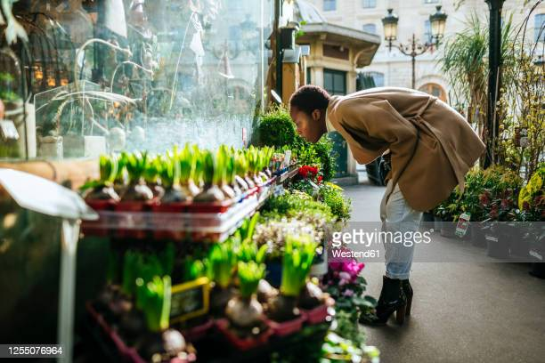 woman smelling flowers at market in paris, france - france stock pictures, royalty-free photos & images