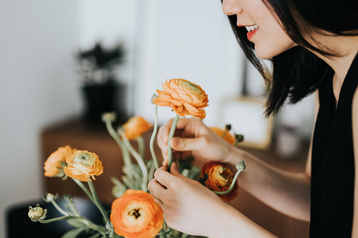 Woman smelling flowers while arranging it at home - gettyimageskorea