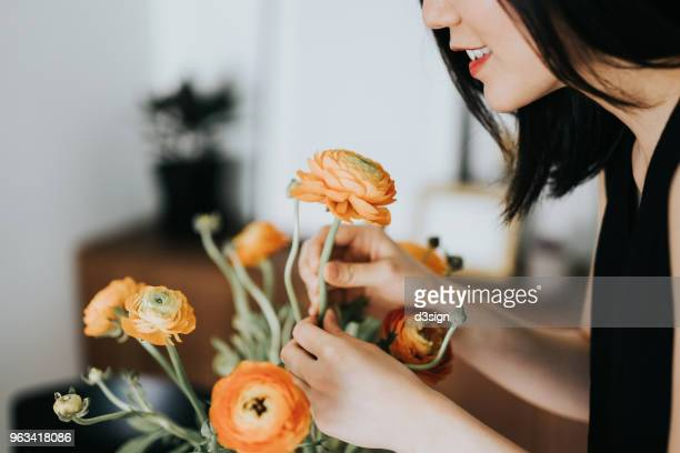 Woman smelling flowers while arranging it at home