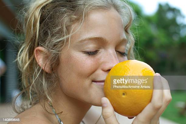 woman smelling fresh orange - freshness stockfoto's en -beelden