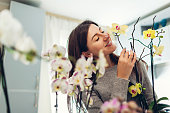 Woman smelling her orchids on kitchen. Housewife taking care of home plants and flowers.