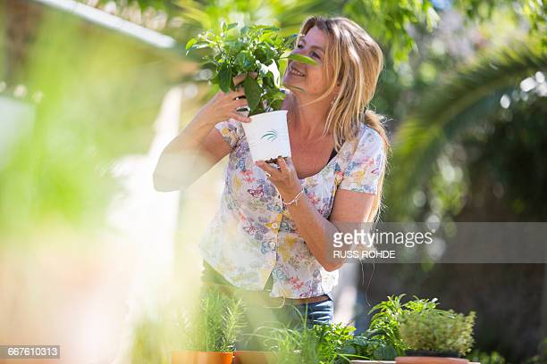 Woman smelling herb plant in garden