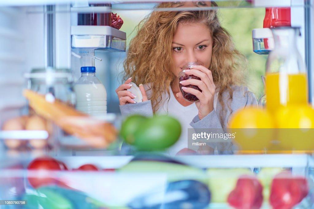 食料品でいっぱい冷蔵庫の前でジャムの臭いがする女。 : ストックフォト