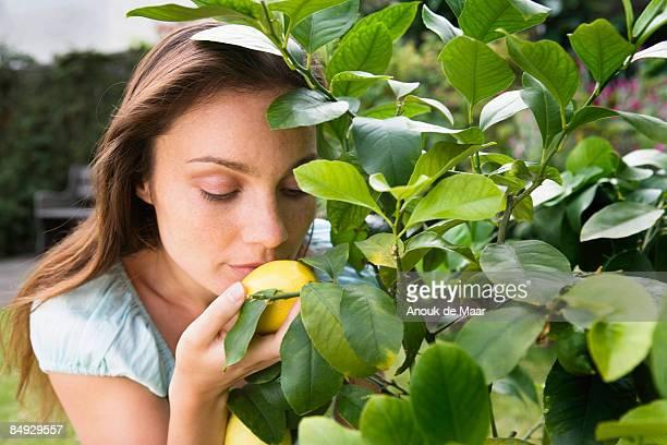Woman smelling lemon on lemon tree