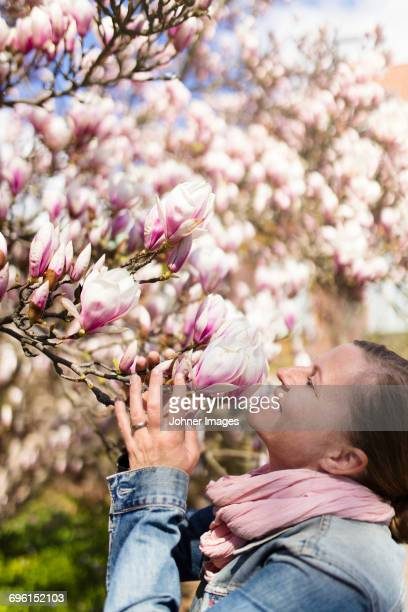Woman smelling magnolia flowers