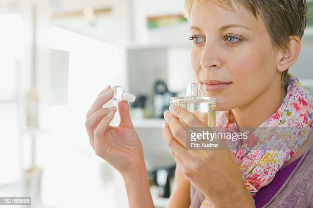 woman smelling perfume in a store - mid adult stock pictures, royalty-free photos & images