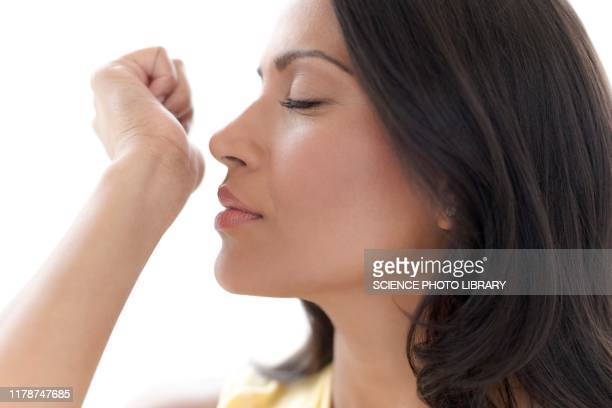 woman smelling perfume on her wrist - one woman only stock pictures, royalty-free photos & images