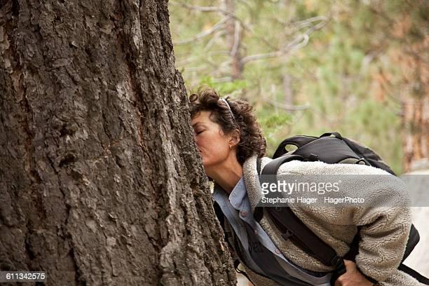 Woman smelling pine tree