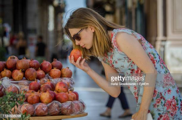Woman Smelling Pomegranate In Market