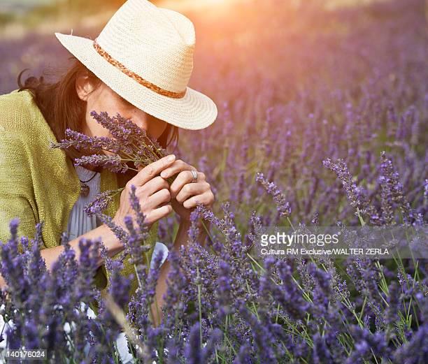Woman smelling purple flowers in field
