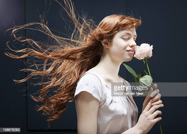 woman smelling rose.