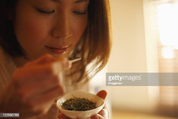 A woman smelling tea leaves