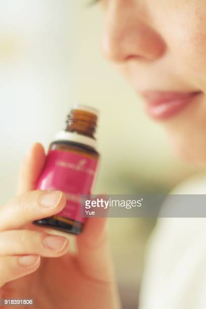 woman smelling the essential oil - aromatherapy oil stock pictures, royalty-free photos & images