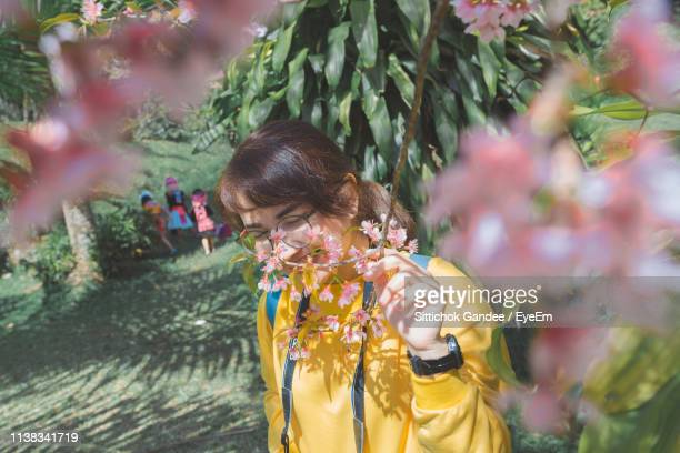 Woman Smelling While Standing By Flowers On Tree