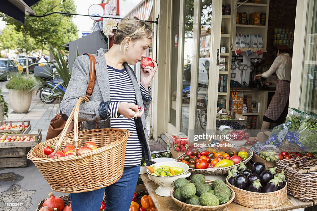 Woman smells fruit shopping in fruitstall. : Stock Photo
