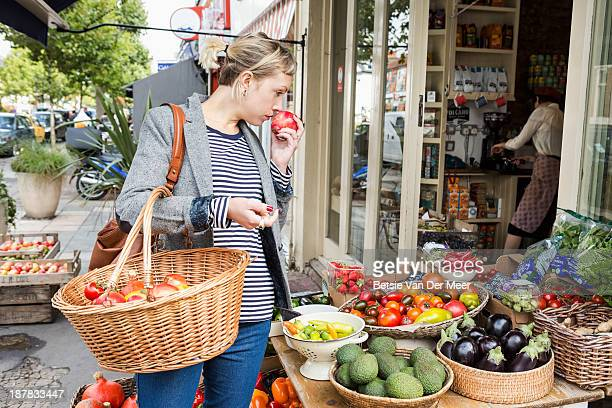 Woman smells fruit shopping in fruitstall.