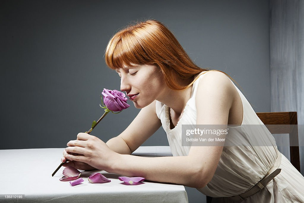 Woman smells rose, sitting at table. : Stock Photo