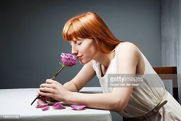 Woman smells rose, sitting at table.