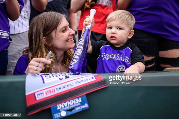 A woman smiles after her son receives an autograph during the spring training game between the Oakland Athletics and Colorado Rockies at Salt River...