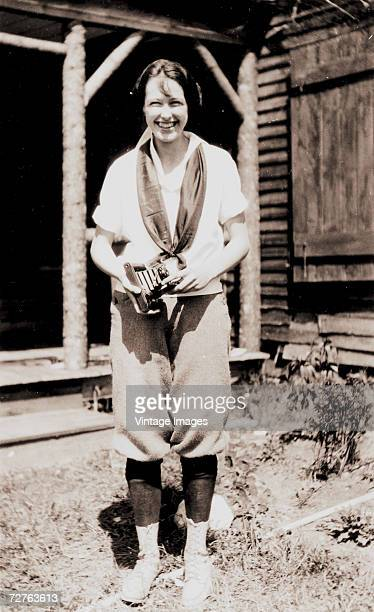 A woman smiles and holds a folding pocket camera outside of a wooden structure 1920s