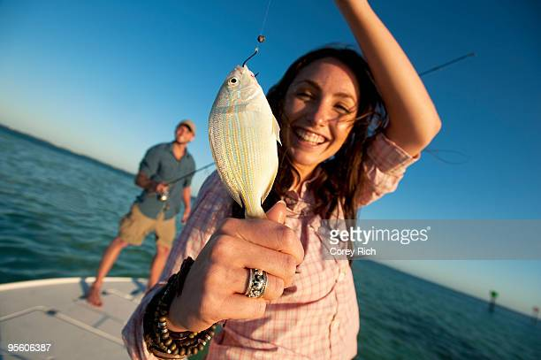 a woman smiles and holds up a small fish in florida. - florida keys stock pictures, royalty-free photos & images