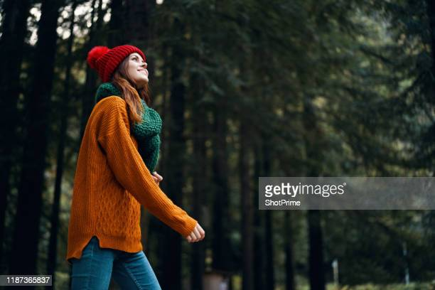 woman smiles and walks in the forest looking at nature, beautiful forest - orange dress stock pictures, royalty-free photos & images