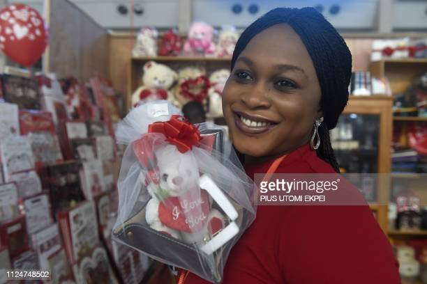 A woman smiles as she holds in the lobby of the Muritala Mohammed 2 Airport in Lagos on February 13 2019 on the eve of Valentine's Day As Nigeria...
