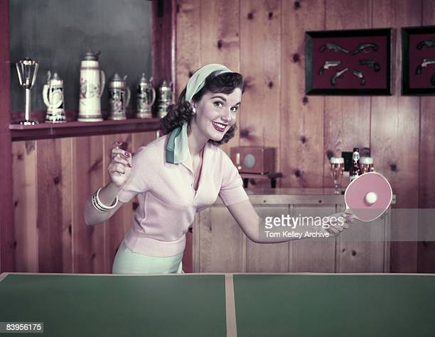 A woman smiles as she returns a shot in ping pong while playing in a woodpanelled beerstein decorated game room ca1950s United States