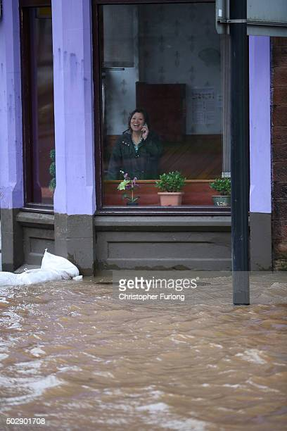 Woman smiles as she speaks on her phone as she looks out from a shop front out as the River Nith bursts its banks on December 30, 2015 in Dumfries,...