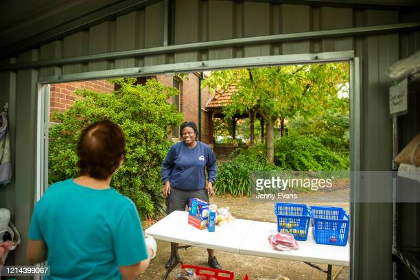 A woman smiles as she waits for food items at St Paul's Anglican Church in Burwood on March 24 2020 in Sydney Australia The Parish Pantry provides...