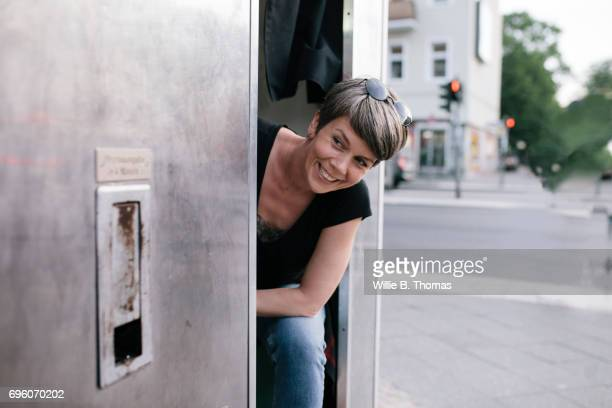 Woman Smiles As She Waits For Photos From a Photo booth