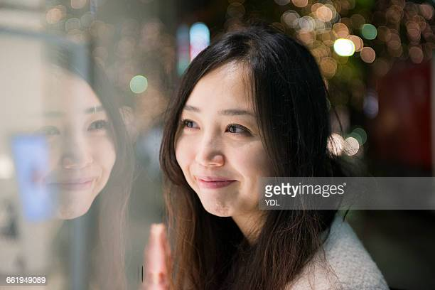 A woman smiles at her reflection in a glass.