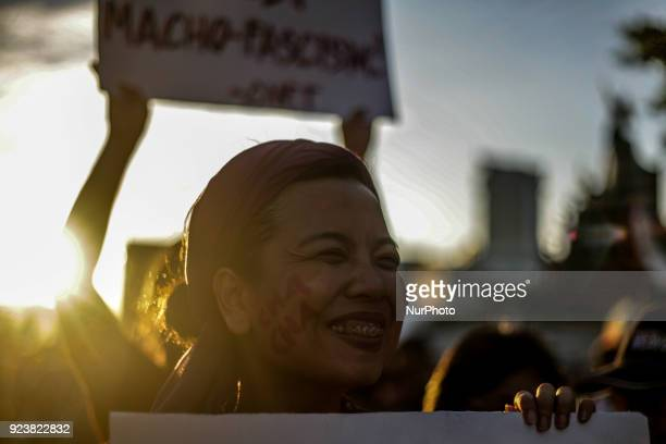 A woman smiles during a protest ahead of the 32nd anniversary of the EDSA People Power Revolution at the People Power Monument in Manila Philippines...