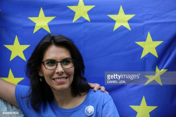 A woman smiles in front of a European Union flag during a picnic against Brexit organised by the General Assembly in Green Park in London on July 9...