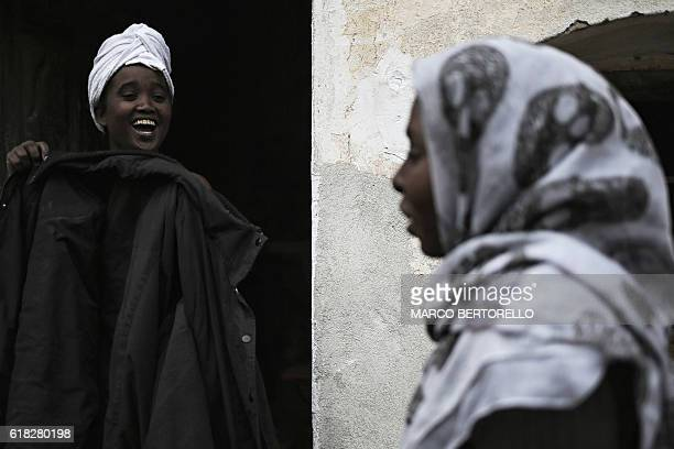 A woman smiles in the courtyard of the house of Francoise Cotta a French citizen who hosts migrants arriving illegally from Italy on October 25 2016...