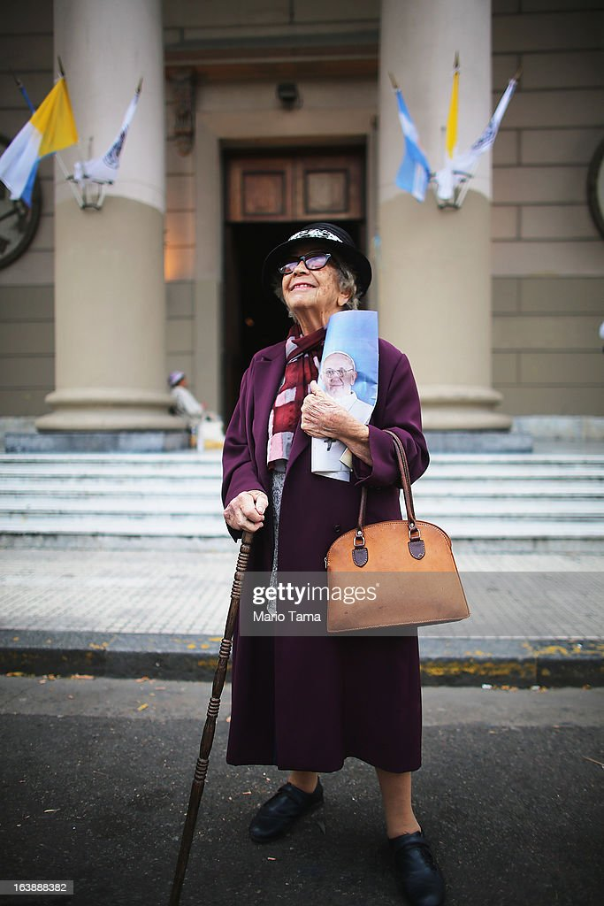 A woman smiles while posing with her image of Pope Francis following Sunday Mass honoring Francis outside the Metropolitan Cathedral on March 17, 2013 in Buenos Aires, Argentina. Francis was the archbishop of Buenos Aires and is the first Pope to hail from South America.