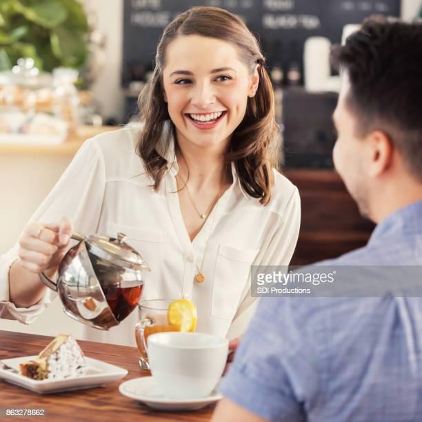 Frau lächelt, während Sie eine Tasse heißen Tee gießen