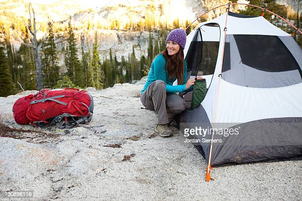 A woman smiles while setting up camp.