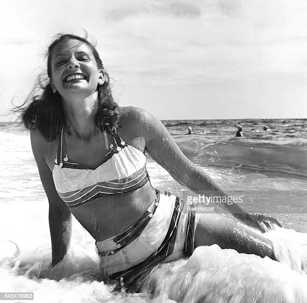 A woman smiles while sitting on the beach as the surf rolls Provincetown Massachusetts 1948