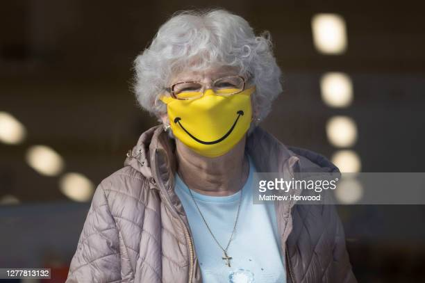 Woman smiles while wearing a novelty face mask in a shop on October 1, 2020 in Barry, Wales. Six more people have died in Wales after testing...