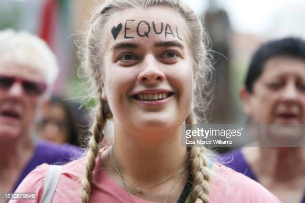 A woman smiles with the word 'equal' written on her forehead as she gathers in Hyde Park during the Sydney International Women's Day march on March...