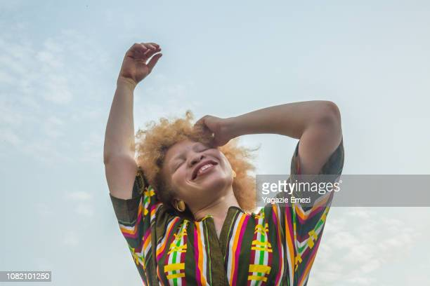 Woman smiling against sky.