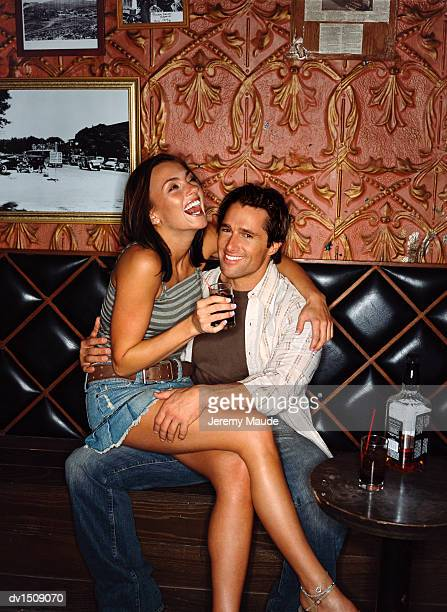 woman smiling and drinking whisky and sitting on a man's lap in a bar - woman sitting on man's lap stock pictures, royalty-free photos & images
