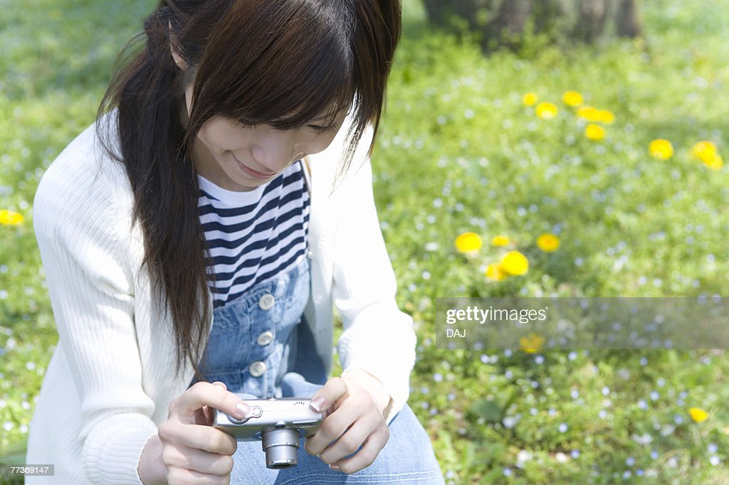 Woman smiling and holding a digital camera on lawn, front view, Japan : Stock Photo