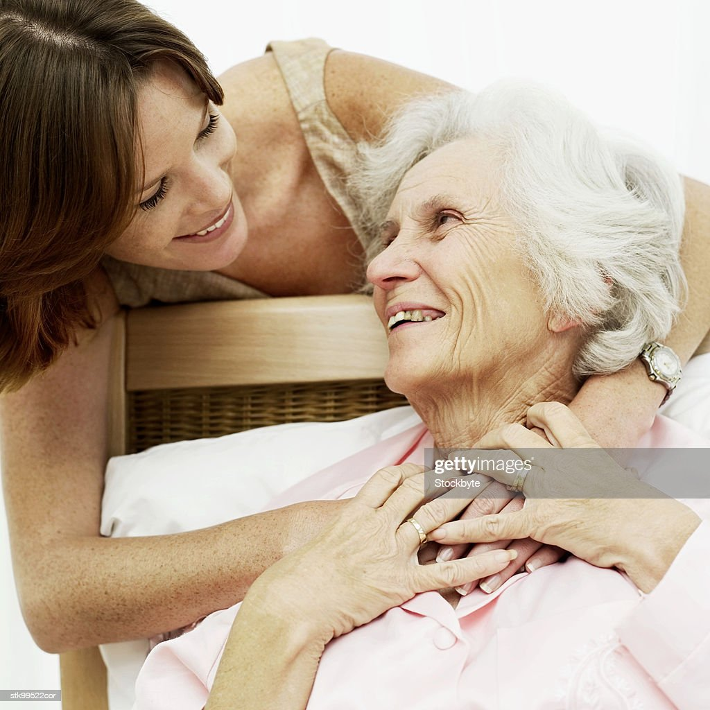 woman smiling and holding an old woman in bed : Stock Photo
