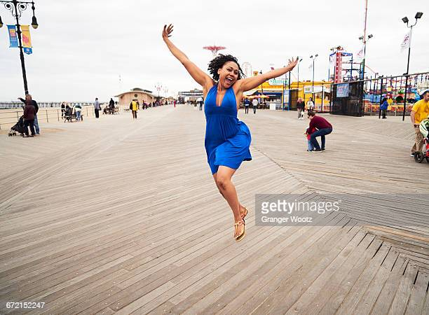 woman smiling and jumping on boardwalk at amusement park - boardwalk stock pictures, royalty-free photos & images