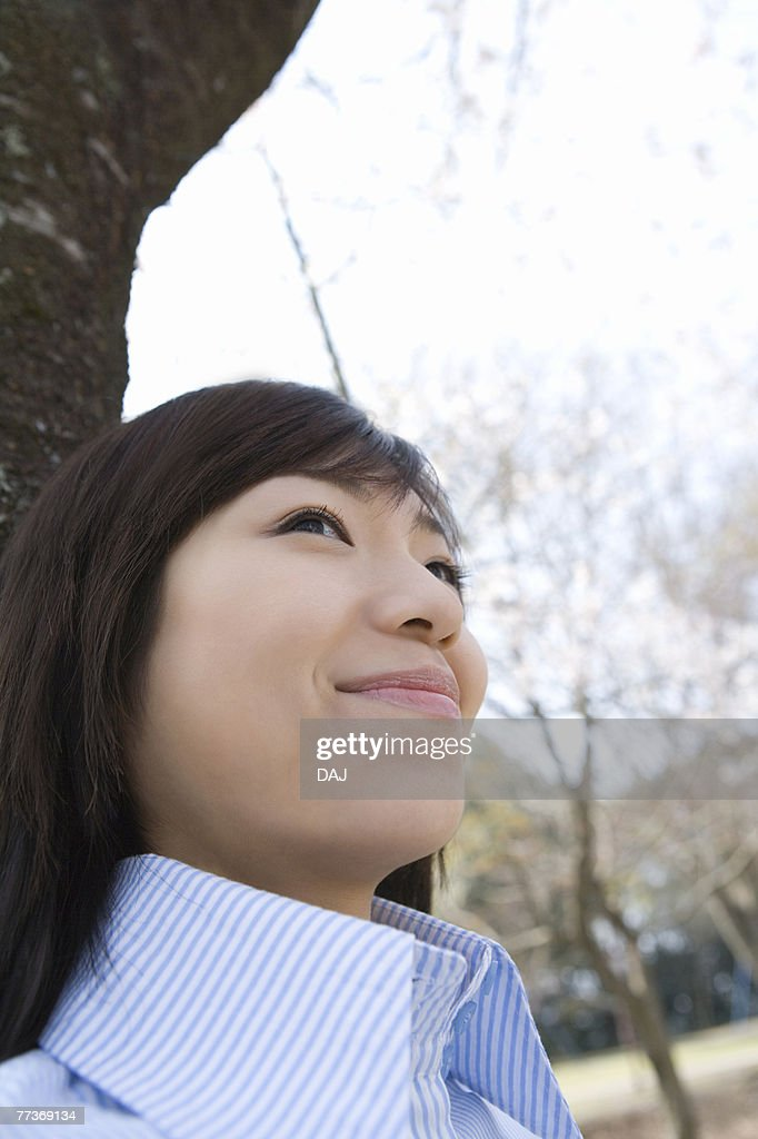 Woman smiling and leaning on a tree trunk, low angle view, side view, Japan : Photo