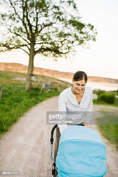 Woman smiling and looking at baby carriage on road