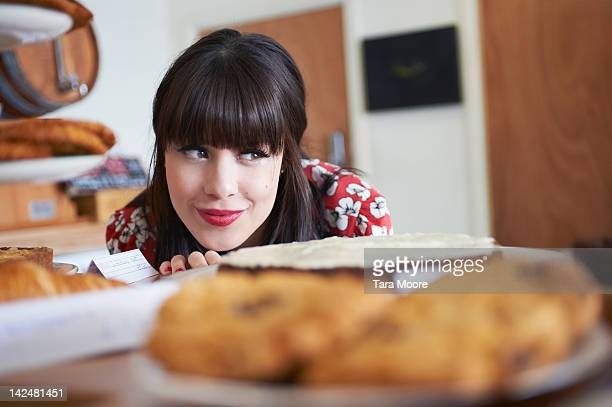woman smiling and looking at cakes in cafe