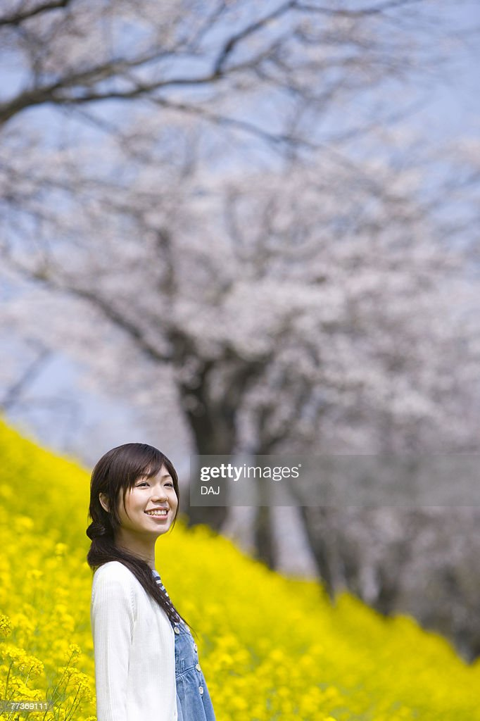 Woman smiling and standing in rape field, side view, Japan : Photo
